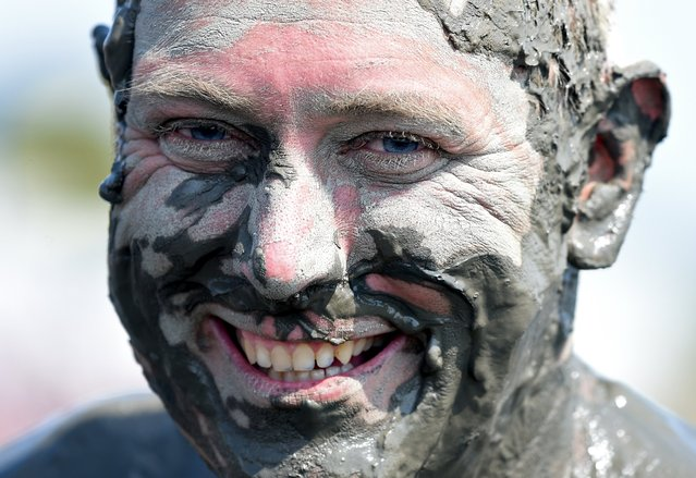 """A player laughs after a handball match at the so called """"Wattoluempiade"""" (Mud Olympics) in Brunsbuettel at the North Sea, July 11, 2015. (Photo by Fabian Bimmer/Reuters)"""