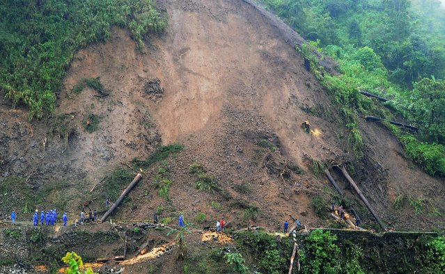 Rescuers and government workers clear a road after landslides brought on by torrential monsoon rains, killed two people on Kennon Road at Benguet province in northern Philippines July 13, 2015. Torrential monsoon rains killed at least eight people in the Philippines, the country's disaster relief agency said on Monday, and the toll was expected to rise as two tropical storms battered northern Luzon, the main island in the archipelago. (Photo by Harley Palangchao/Reuters)