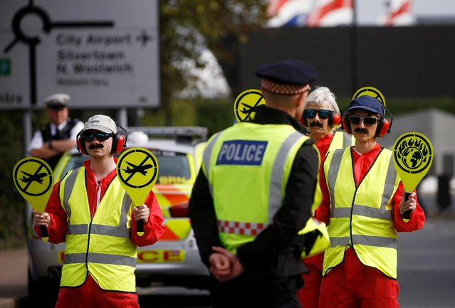 Extinction Rebellion protesters dressed as airport marshalls block the road during a demonstration, near London City Airport, in London, Britain, October 10, 2019. Some hundreds of climate change activists are in London during a fourth day of world protests by the Extinction Rebellion movement to demand more urgent actions to counter global warming. (Photo by Henry Nicholls/Reuters)