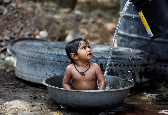 A baby girl cools off as her mother (not pictured) fills the tub with water on a hot summer day, outside a farm on the outskirts of Ahmedabad, India May 2, 2017. (Photo by Amit Dave/Reuters)