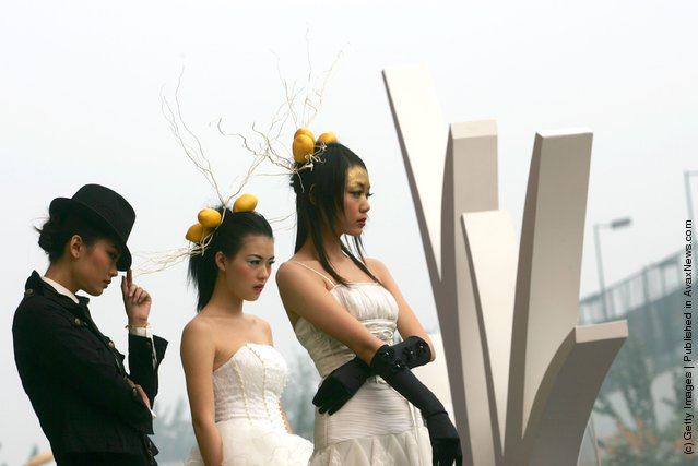 Models promote architectural designs for apartment blocks during the 2007 Xian Autumn Real Estate Trade Fair