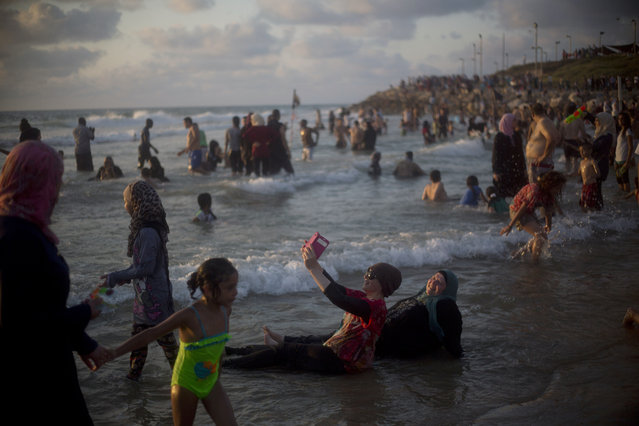 Palestinians, many of whom came from the West Bank, bathe in the Mediterranean Sea during the last day of the Eid al-Fitr holiday as the sun sets in Tel Aviv, Israel, Sunday, July 19, 2015. (Photo by Ariel Schalit/AP Photo)
