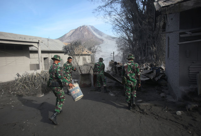 Indonesian soldiers set up a road block to prevent people from entering the danger zone following the eruption of Mount Sinabung in Gamber village, North Sumatra, Indonesia, Sunday, May 22, 2016. (Photo by Binsar Bakkara/AP Photo)
