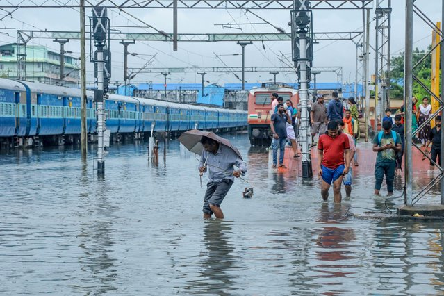 Passengers walk on waterlogged rail tracks at Ernakulam Junction station in Kochi in the southwestern Indian state of Kerala on October 21, 2019. (Photo by AFP Photo/Stringer)