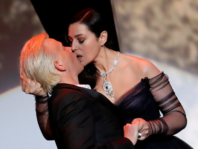 Italian actress and master of ceremonies Monica Bellucci (R) and French comedian Alex Lutz kiss as they perform on stage on May 17, 2017 during of the opening ceremony of the 70 th edition of the Cannes Film Festival in Cannes, southern France. (Photo by Eric Gaillard/Reuters)