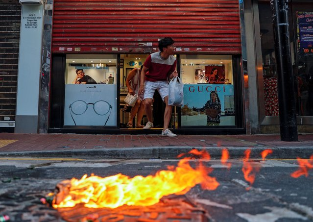 "A fire is seen in front of an optician's after anti-government bill protesters threw the Molotov cocktails during a march billed as a global ""emergency call"" for autonomy, in Hong Kong, China on November 2, 2019. (Photo by Tyrone Siu/Reuters)"