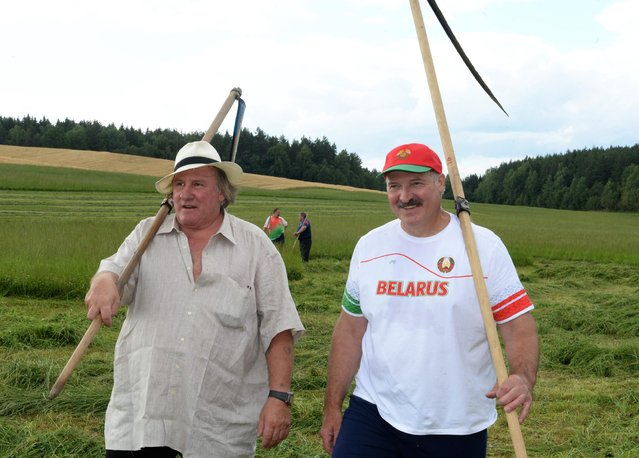 In this photo taken Wednesday, July 22, 2015, Belarus' President Alexander Lukashenko and French actor Gerard Depardieu, left, hold hand scythes as they walk in the presidential residence of Ozerny, outside Minsk, Belarus. Depardieu has frequented the former Soviet Union for years before he took Russian citizenship in 2013 in a bid to escape sky-high taxes in France. He has recently attracted the wrath of the Ukrainian government by condoning Russia's annexation of Crimea. (Photo by Andrei Stasevich/BelTA Photo via AP Photo)