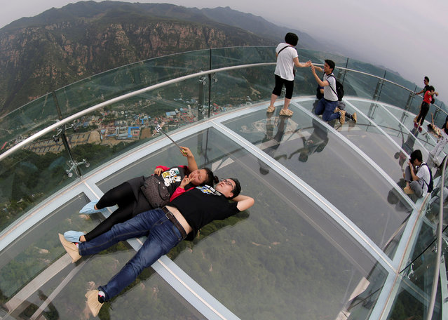 A couple takes a selfie on the glass sightseeing platform on Shilin Gorge in Beijing, China, May 27, 2016. (Photo by Kim Kyung-Hoon/Reuters)