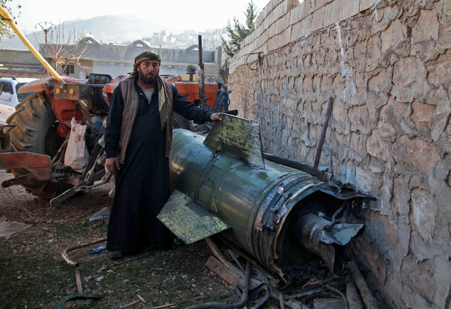 A Syrian man stands next to a fragment of a ground-to-ground missile fired by regime forces and hit a makeshift camp in the village of Qah near the Turkish border in the northwestern Idlib province on November 21, 2019. The Syrian Observatory for Human Rights, in an updated toll, said a ground-to-ground missile fired by regime forces that hit a makeshift camp for the displaced near Qah village close to the border with Turkey killed 15 civilians, including six children, and wounded around 40 others. The missile crashed near a maternity facility in the camp, it said. (Photo by Aaref Watad/AFP Photo)