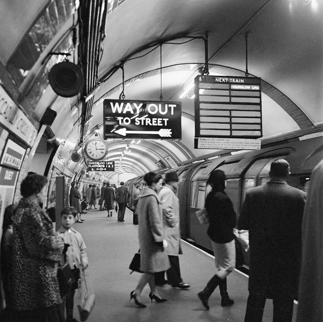 "Piccadilly Circus Station, London, 1960-1965. Platform at Piccadilly Circus underground station showing people entering a Hounslow Line train, and the ""Way Out"" sign above. (Photo by English Heritage/Heritage Images/Getty Images)"