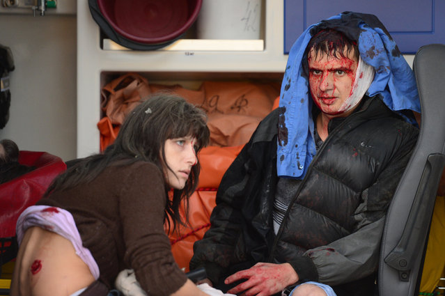 Two people sit in an ambulance waiting to be treated after a Grad rocket slammed into a shopping mall in Donetsk's Kubishevski district, in the eastern Ukraine,  on October 8, 2014. At least two people were killed, and five were injured after some six Grad rockets hit the area. (Photo by John Macdougall/AFP Photo)