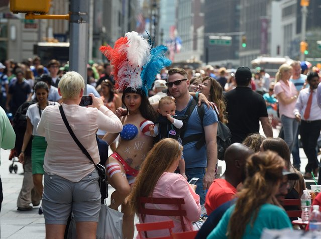 A young woman poses with tourists in Times Square wearing body paint to cover herself August 19, 2015 in New York. (Photo by Don Emmert/AFP Photo)