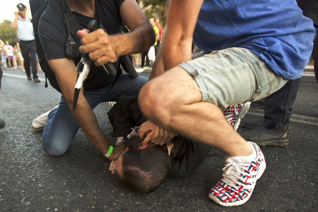 A police officer removes a knife from ultra-Orthodox Jew Yishai Schlissel after he stabbed people during a gay pride parade in Jerusalem on Thursday, July 30, 2015. Schlisse was recently released from prison after serving a term for stabbing several people at a gay pride parade in 2005, a police spokeswoman said. (Photo by Sebastian Scheiner/AP Photo)
