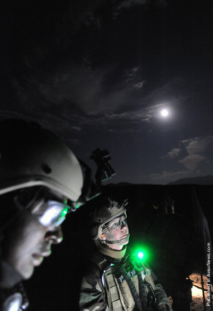 Mass Communication Specialist 1st Class Denise Martin, right, assigned to Fleet Combat Camera Group Pacific, inspects a target during a night weapons shoot as part of the Fleet Combat Camera Group Pacific Summer Quick Shot 2011