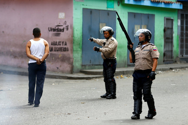 Riot police officers patrol a neighborhood after a protest over food shortage and against Venezuela's government in Caracas, Venezuela, June 10, 2016. (Photo by Ivan Alvarado/Reuters)