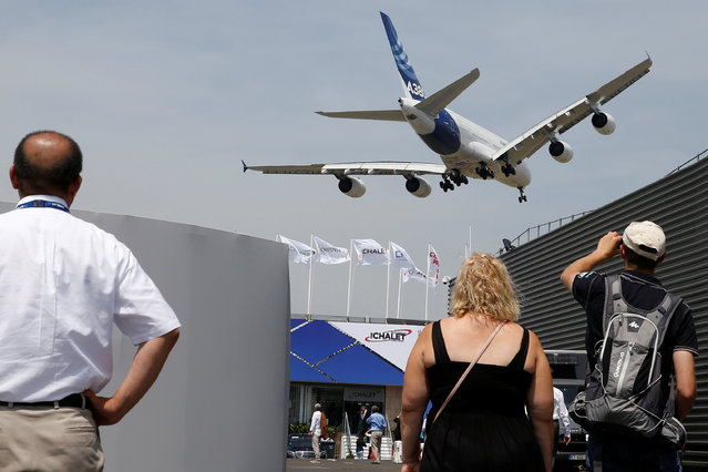 People look at an Airbus A380 as it takes part in flying display during the 52nd Paris Air Show at Le Bourget Airport near Paris on June 22, 2017. (Photo by Pascal Rossignol/Reuters)