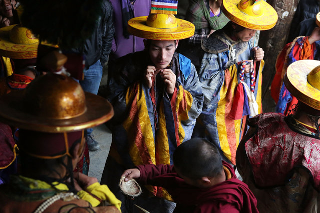 Elaborately dressed monks prepare to perform ceremonies in the main square during the Tenchi Festival on May 25, 2014 in Lo Manthang, Nepal. The Tenchi Festival takes place annually in Lo Manthang, the capital of Upper Mustang and the former Tibetan Kingdom of Lo. Each spring, monks perform ceremonies, rites, and dances during the Tenchi Festival to dispel evils and demons from the former kingdom. (Photo by Taylor Weidman/Getty Images)