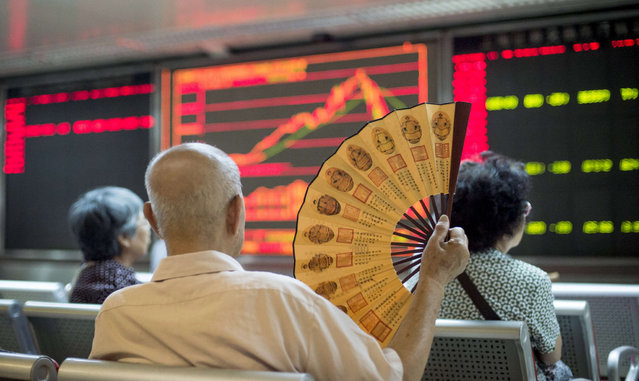 Investors look at screens showing stock market movements at a securities company in Beijing on July 28, 2015. Chinese shares sank on July 28, a day after Shanghai's steepest one-day slide in eight years, defying renewed government vows of support that analysts warned were not enough to soothe nervous investors. (Photo by Fred Dufour/AFP Photo)