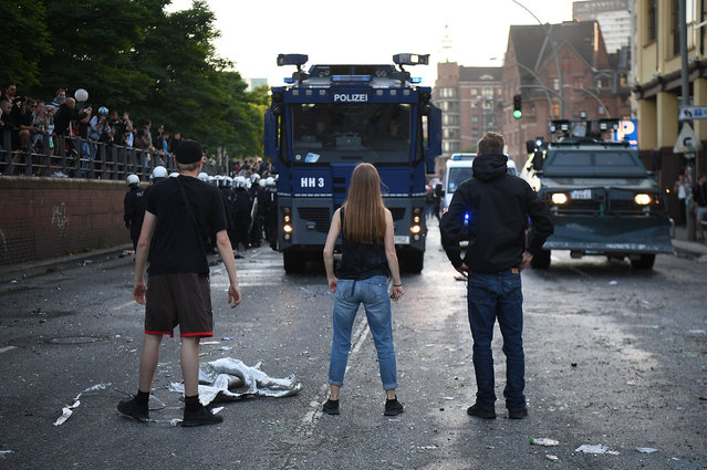 "People stand in front of police vehicles during the ""Welcome to Hell"" protest march on July 6, 2017 in Hamburg, Germany. Leaders of the G20 group of nations are arriving in Hamburg today for the July 7-8 economic summit and authorities are bracing for large-scale and disruptive protest efforts tonight at the ""Welcome to Hell"" anti-G20 protest. (Photo by Leon Neal/Getty Images)"
