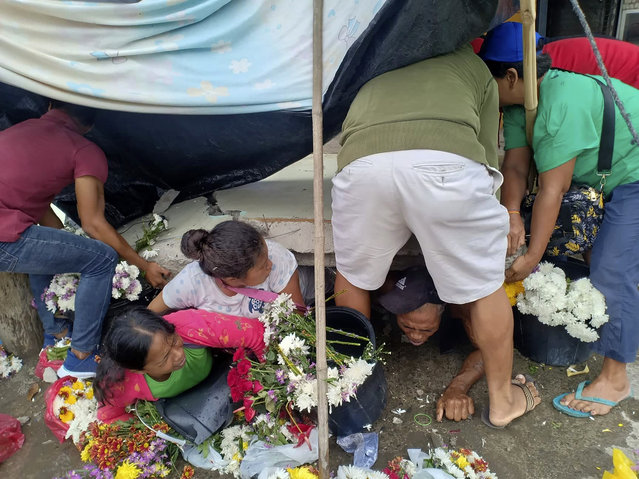 Trapped flower vendors are pulled out from a collapsed wall following a strong earthquake that struck Padada, Davao del Sur province, southern Philippines on Sunday December 15, 2019. A strong quake jolted the southern Philippines on Sunday, causing a three-story building to collapse and prompting people to rush out of shopping malls, houses and other buildings in panic, officials said. (Photo by John Angelo Jomao-as/AP Photo)