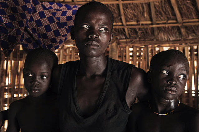Mandelina Nyi-Bo (C), an ethnic Jur, sits in her bamboo hut with her daughters Jore (R) and Nyankuru in the remote village Dongoi in Western Equatorial State, April 7, 2010. Nyi-Bo's husband was killed in ethnic clashes with the Dinka tribewhile she fled with her children from her home village of Lamo. (Photo by Finbarr O'Reilly/Reuters)
