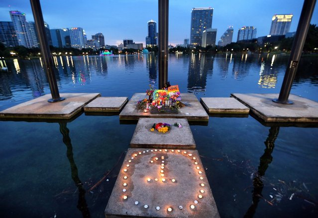 "The symbol for ""One Orlando"" is spelled out at a makeshift memorial at Lake Eola in downtown Orlando, Fla., Saturday, June 18, 2016. Nearby, visitors lit candles and prayed at a larger memorial, at the Dr. Phillips Center for the Performing Arts, to mourn the victims of the Pulse massacre. (Photo by Joe Burbank/Orlando Sentinel via AP Photo)"