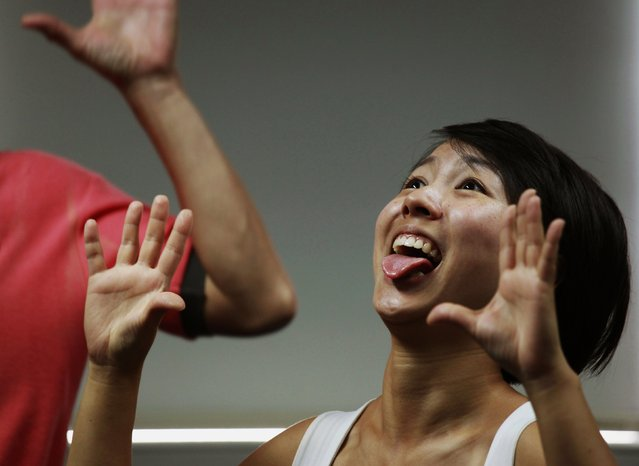 """A staff member from Ocean Park reacts during a Laughter Yoga class in Hong Kong July 10, 2014. Consultancy firm """"Inspire 2 Aspire"""" run Laughter Yoga classes for corporations which partner Mahesh Pamnani believes ease stress and increases productivity and creativity among staff. Laughter Yoga was first developed 1995 in Mumbai, India by Dr. Madan Kataria, and has over 600 clubs in 60 countries, according to Laughter Yoga International. (Photo by Bobby Yip/Reuters)"""