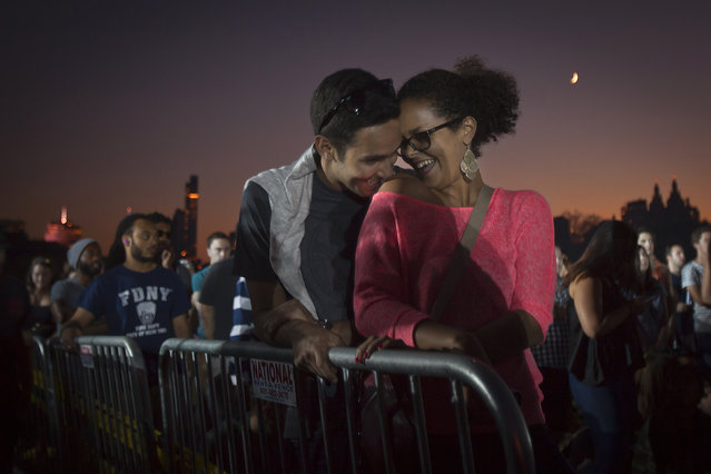 A couple shares an intimate moment during the Global Citizen Festival concert in Central Park in New York September 27, 2014. (Photo by Carlo Allegri/Reuters)