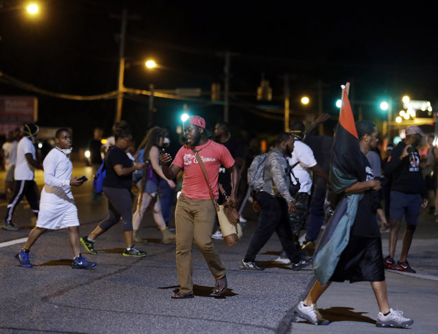 Protesters walk on the street, Monday, August 10, 2015, in Ferguson, Mo. Ferguson was a community on edge again Monday, a day after a protest marking the anniversary of Michael Brown's death was punctuated with gunshots. (Photo by Jeff Roberson/AP Photo)