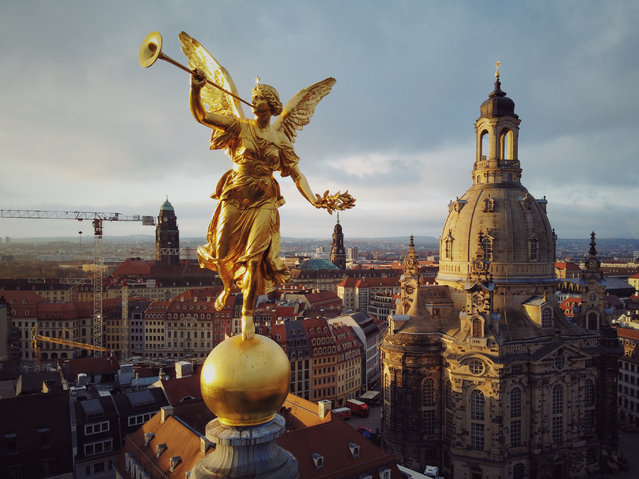 The golden sculpture of Pheme, the personification of fame and renown in Greek mythology, on the roof of the Dresden University of Visual Arts in Dresden, Germany on November 30, 2019, with the rebuilt Frauenkirche, which was destroyed in World War II bombing, in the background. (Photo by Amos Chapple/Radio Free Europe/Radio Liberty)