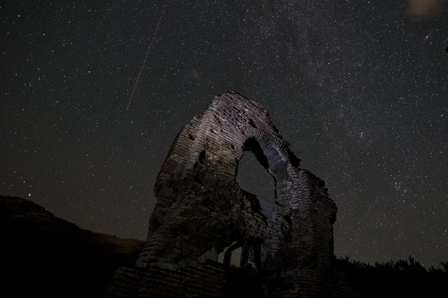 A long exposure image showing an aeroplane passing in the sky during the Perseids meteor shower over the remains of St. Ilia Roman early Christian basilica dated back to the 5th6th century AD near the town of Pirdop, early on August 12, 2015. (Photo by Nikolay Doychinov/AFP Photo)