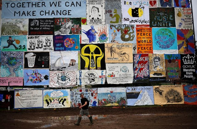 A reveller walks near a wall with posters at Worthy Farm in Somerset during the Glastonbury Festival, Britain June 23, 2016. (Photo by Stoyan Nenov/Reuters)