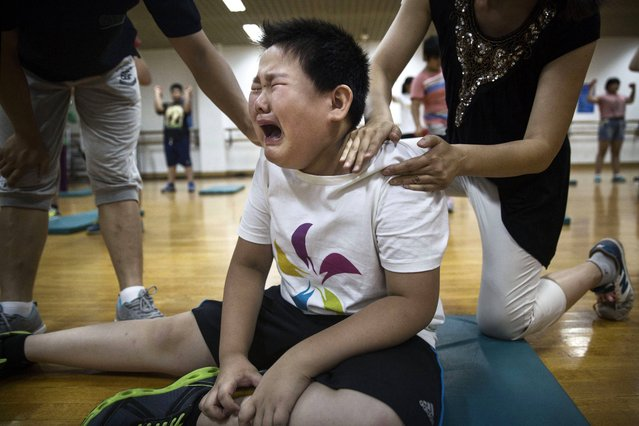 An overweight Chinese student weeps after a light exercise during training at a camp held for overweight children at a local university on July 16, 2014 in Beijing, China. Obesity is a growing problem amongst the burgeoning middle-class in China, and recent studies show that the country is now the second fattest in the world behind the United States. (Photo by Kevin Frayer/Getty Images)
