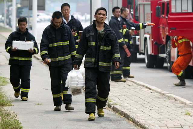 Chinese firefighter collect lunch as they wait near the site of an explosion in northeastern China's Tianjin municipality Saturday, August 15, 2015. (Photo by Ng Han Guan/AP Photo)
