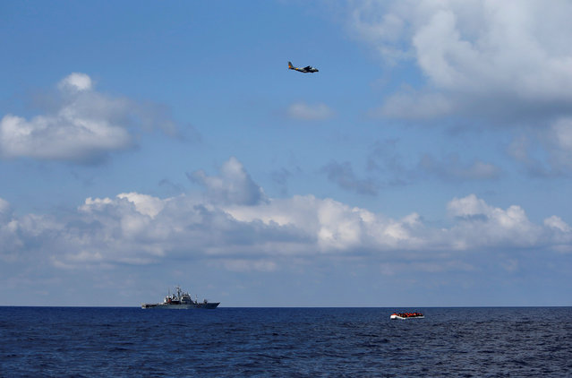 A Spanish plane and Italian Navy ship pass near migrants in a dinghy awaiting rescue by the Migrant Offshore Aid Station (MOAS), around 20 nautical miles off the coast of Libya, June 23, 2016. (Photo by Darrin Zammit Lupi/Reuters)