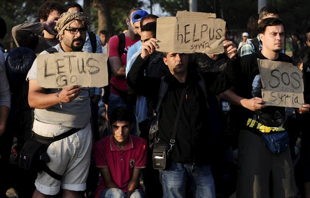 People, part of a new group of more than a thousand immigrants, hold placards as they wait at the border line of Macedonia and Greece to enter into Macedonia near Gevgelija railway station August 20, 2015. (Photo by Ognen Teofilovski/Reuters)
