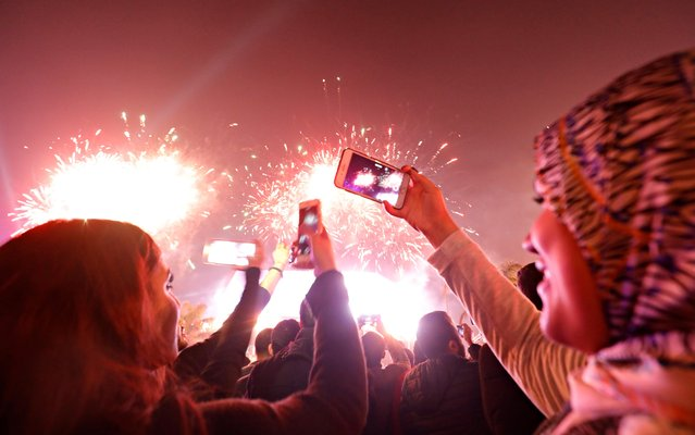 People record fireworks on mobile phones during a New Year celebrations at the Waterway in Cairo, Egypt on January 1, 2020. (Photo by Amr Abdallah Dalsh/Reuters)
