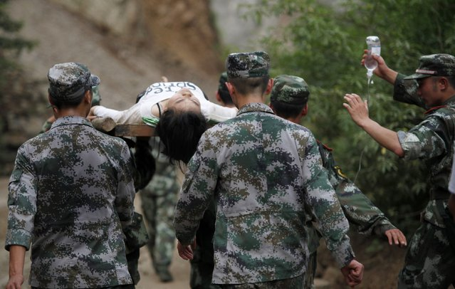 Paramilitary policemen carry an injured woman with a stretcher after an earthquake hit Ludian county of Zhaotong, Yunnan province August 3, 2014. The magnitude 6.5 earthquake struck southwestern China on Sunday, killing at least 175 people and leaving more than 180 missing and 1,400 injured in a remote area of Yunnan province, causing thousands of buildings, including a school, to collapse, Xinhua News Agency reported. (Photo by Reuters/China Daily)