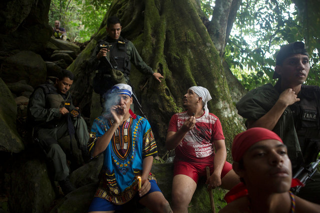 People smoke cigars next to Venezuelan National Guards at the Maria Lionza shrine on the Sorte Mountain on the outskirts of Chivacoa, in the state of Yaracuy, Venezuela October 11, 2015. (Photo by Marco Bello/Reuters)
