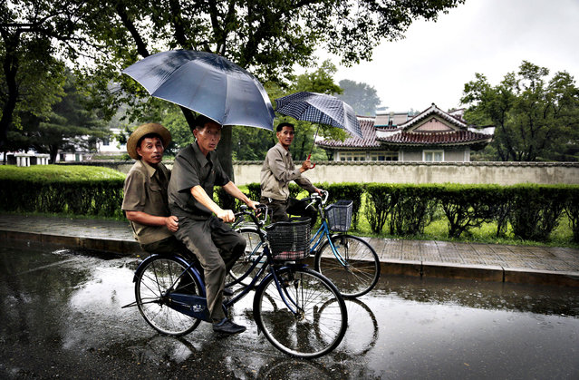 North Korean men cycle in the rain past homes built for farmers at the Mangyongdae Cooperative Farm, Wednesday, July 30, 2014 in Pyongyang, North Korea. As the planting season ends and the rainy season begins, North Koreans are girding for the possibility of floods, which, after weeks of drought, have already caused some damage across wide swaths of the nation. (Photo by Wong Maye-E/AP Photo)