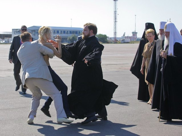 A topless protester from the Ukrainian feminist group Femen is blocked by a security guard and a priest as she tries to throw herself at the leader of the Russian Orthodox Church