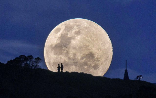 Walkers silhouetted against the moon in Auckland, New Zealand. (Photo by Simon Runting/Rex Features/SIPA Press)