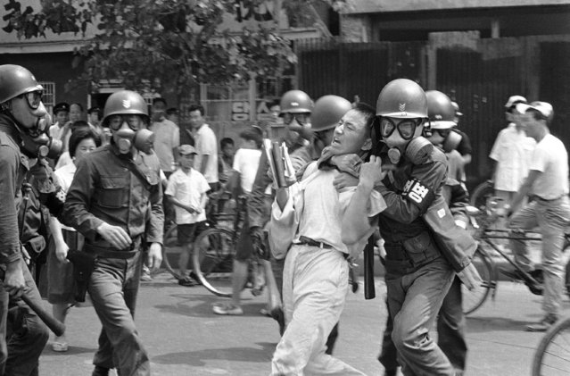 "South Korean Army troops, wearing gas masks, take a student demonstrator into custody during outbreak in capital city of Seoul on August 25, 1965. The students are protesting against the government of President Chung Hee Park and its friendship treaty with Japan. Park has threatened to shut down South Korea's schools ""semi permanently"" unless the demonstrations are stopped. (Photo by AP Photo)"
