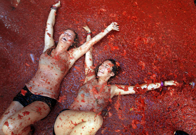 "Two woman lie in a puddle of squashed tomatoes during the annual ""Tomatina"" tomato fight fiesta, in the village of Bunol, 50 kilometers outside Valencia, Spain, Wednesday, August 26, 2015. The streets of an eastern Spanish town are awash with red pulp as thousands of people pelt each other with tomatoes in the annual ""Tomatina"" battle that has become a major tourist attraction. (Photo by Alberto Saiz/AP Photo)"