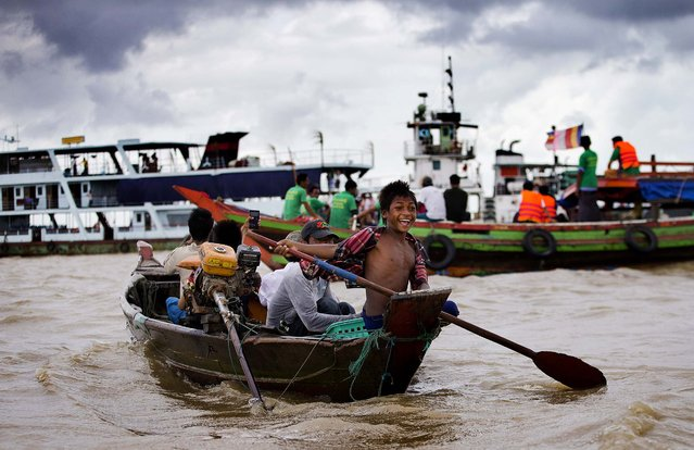 A boy peddles a boat with passengers who came to see the recovery efforts of an ancient bell in a river in Yangon, Myanmar, on August 15, 2014. Divers attached to safety ropes have plunged into waters south of Myanmar's old capital as part of renewed efforts to retrieve a bronze bell that has been lying for centuries at the confluence of three rivers. (Photo by Gemunu Amarasinghe/AP Photo)