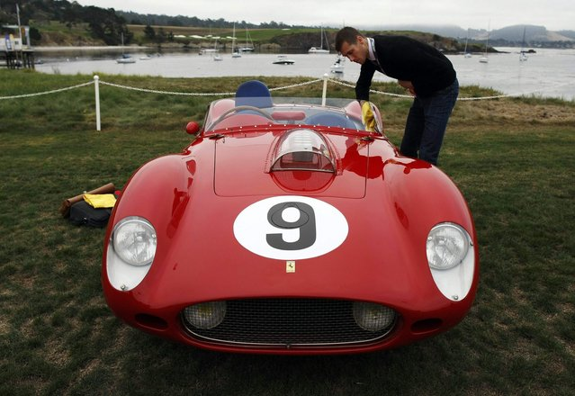 A man cleans a 1959 Ferrari 250 TR59 Fantuzzi Spyder during the Concours d'Elegance on the 18th fairway of the Pebble Beach Golf Links in Pebble Beach, California, August 17, 2014. (Photo by Michael Fiala/Reuters)