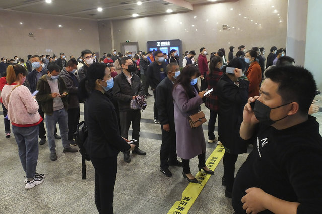 Travelers wearing masks line up to buy train tickets at a railway station in Yichang in central China's Hubei province Wednesday, March 25, 2020. Trains carrying factory employees back to work after two months in locked-down cities rolled out of Hubei province, the center of China's virus outbreak, as the government on Wednesday began lifting the last of the controls that confined tens of millions of people to their homes. (Photo by Chinatopix via AP Photo)