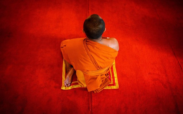 A Thai Buddhist monk prepares to take part in a televised anti-plague prayer at Wat Traimit Temple (Temple of the Golden Buddha) amid lockdown restrictions to contain the spread of the COVID-19 coronavirus in Bangkok on March 25, 2020. The monks at Buddhist temples nationwide chanted the Rattanasoot (Seven Legends) Prayer in unison in a bid to boost public morale amid the epidemic of COVID-19 coronavirus. (Photo by Mladen Antonov/AFP Photo)