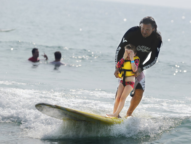 Izzy Paskowitz helps Nixee Grace Chanowsky, 4, catch a wave Monday, August 18, 2014 at Wrightsville Beach, N.C. during the Annual Surfers Healing event for children with autism. Hundreds of people made their way to the beach to watch and cheer on the camp that was founded by Israel and Danielle Paskowitz. (Photo by Mike Spencer/AP Photo/The Star-News)