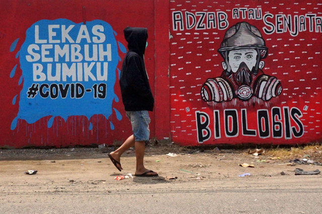 An Indonesian man wearing a face mask walks past murals amid concerns of the COVID-19 coronavirus outbreak in Tangerang on March 29, 2020. Indonesia as of March 28 has declared 1,155 confirmed infections with 102 deaths, making it the country with the highest fatality rate in Southeast Asia. (Photo by Fajrin Raharjo/AFP Photo)